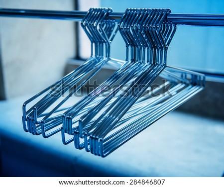 Metallic coat hangers on clothes rail - empty closet - stock photo