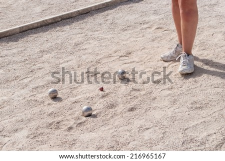 Metallic petanque balls and a small red jack on a fine gravel ground - stock photo