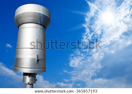 Metallic Rain Gauge on Blue Sky / Weather station with metallic rain gauge on a blue sky with clouds and sun rays - stock photo