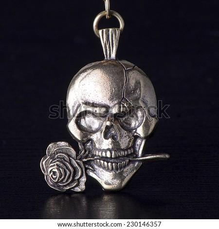 Metallic skull with rose isolated on black background, trinket of bronze.  - stock photo