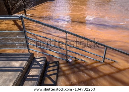 Metallic stair access to a river overflowed. - stock photo