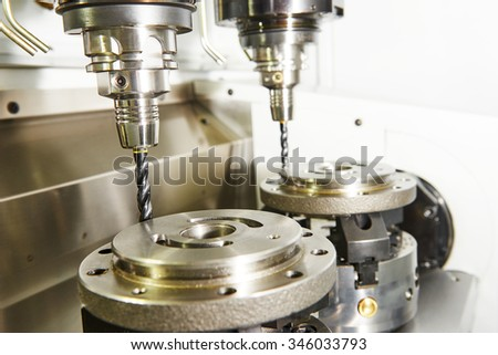 Metalwork industry. Milling machine tool with two mills in chuck preparing to process metal detail at industrial manufacture factory - stock photo