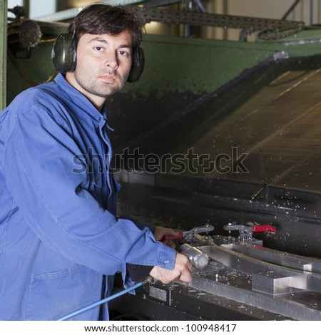Metalworker cleaning a machine in fabric - stock photo