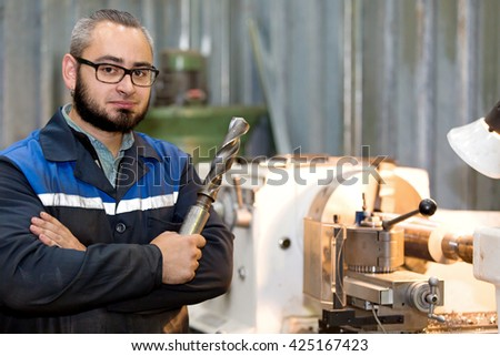 metalworking industry: factory man turner with auger tool on workshop lathe machine background - stock photo