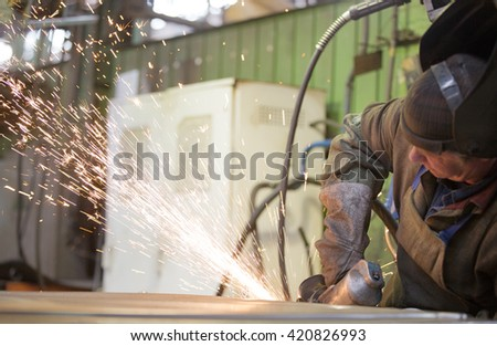 metalworking industry: factory welder worker grinding steel sheet with flying sparks in workshop - stock photo