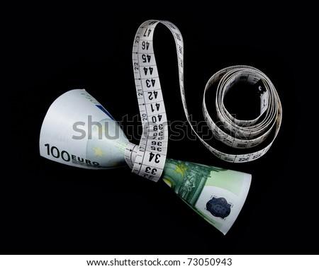 Meter wrapped around 100 euros, on a black background. - stock photo