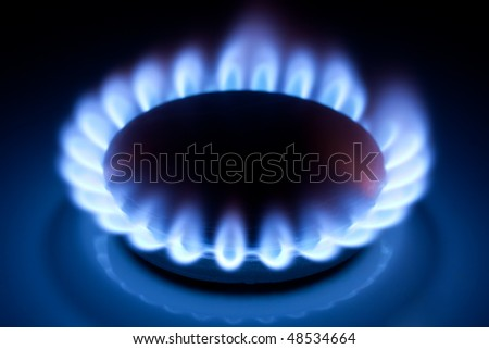 Methane blue flames at kitchen cooker in the dark - stock photo