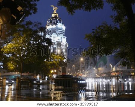metropolis building in madrid illuminated at night - stock photo