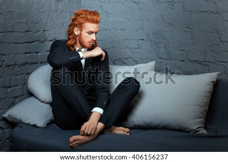 Metrosexual man with red hair and a beard sitting on a couch. - stock photo