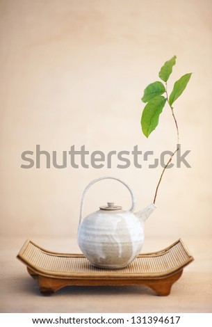 Metta or Lovingkindness.Still life photography of a beautiful asian teapot with a branch of  Spring leaves set upon an organic bamboo tray. - stock photo