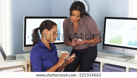 Mexican and African American business women using mobile phones and working together - stock photo