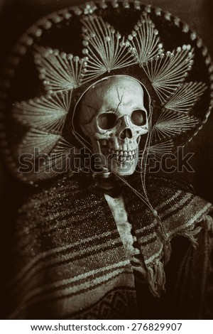 Mexican Bandit Skeleton 8. A skeleton wearing a Mexican sombrero and a poncho. Edited in a vintage film style. - stock photo