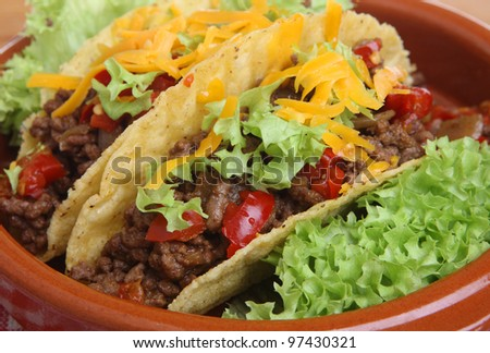 Mexican beef tacos in pottery serving dish - stock photo