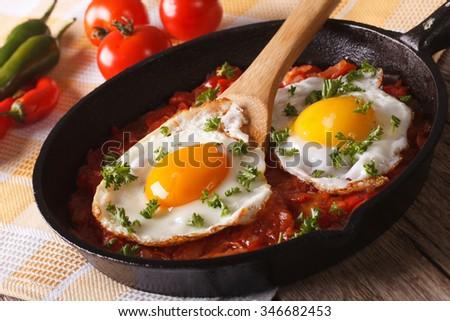 Mexican breakfast huevos rancheros: fried egg with salsa closeup in the pan. Horizontal - stock photo