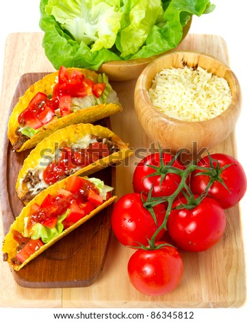 Mexican burrito in tortilla shells with fresh tomatoes, cheese and lettuce - stock photo