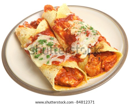 Mexican chicken enchiladas with spicy tomato sauce and cheese. - stock photo