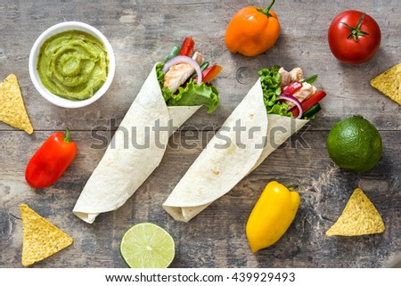 Mexican chicken fajita and ingrendients on a rustic wooden background   - stock photo