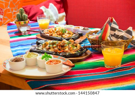 Mexican chicken fajitas with sauces on the table - stock photo