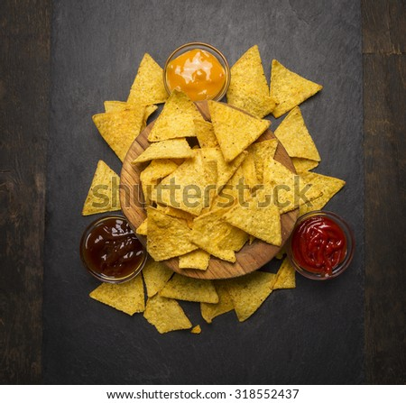 Mexican chips in a wooden bowl with cheese,ketchup, barbecue  sauce on rustic wooden background  close up top view  - stock photo