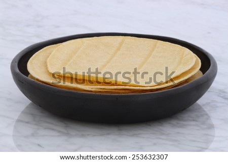 Mexican corn tortillas on retro vintage carrara marble in beautiful terracotta pot, perfect for all your Mexican and tex-mex recipes. - stock photo