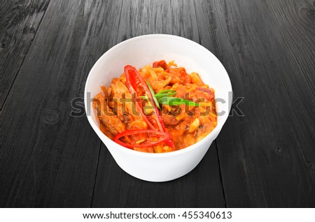Mexican cuisine food delivery - chili con carne in white plastic plate closeup at black wood background - stock photo
