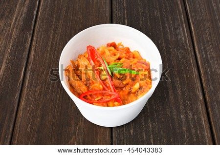 Mexican cuisine food delivery - chili con carne in white plastic plate closeup at brown wood background - stock photo