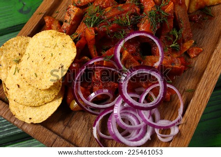 Mexican Cuisine Meat Pieces In Sauce With Fried Potato Onion Rings Chips And Jalapeno