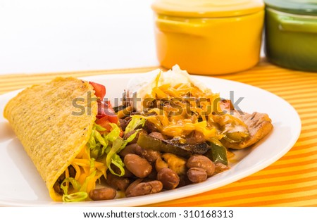 "Mexican Dinner with Tex-Mex Chicken dish ""Pollo Elegante"" with crunchy taco and strong back lighting. - stock photo"
