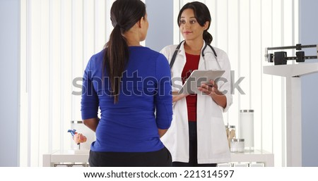 Mexican doctor talking to African American patient using pad - stock photo