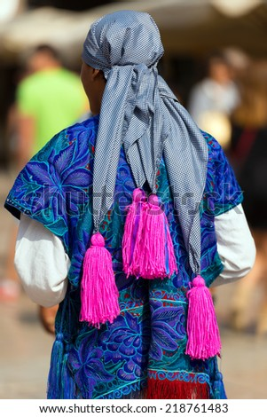 Mexican Dress - Zinacantan Chiapas Mexico / Mexican man with a multi colored dress with floral texture, checkered headdress with fuchsia tassels - Zinacantan Chiapas Mexico - stock photo