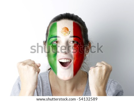 Mexican fan screaming GOAL with hands up and painted flag on her face. - stock photo