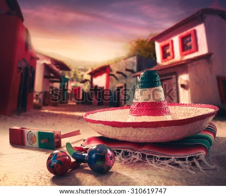"Mexican fiesta background with a hat ""sombrero"" and ""maracas"" in a mexican town - stock photo"