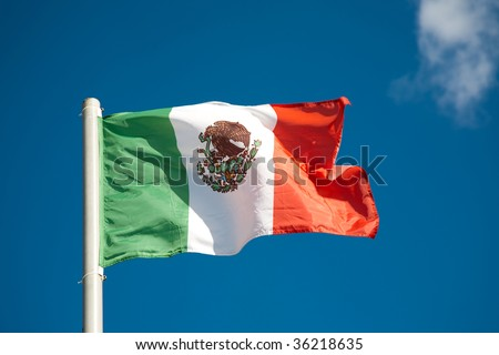 Mexican flag against blue sky - stock photo