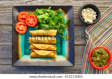 Mexican flautas rolled tacos with salsa and Mexico food ingredients - stock photo