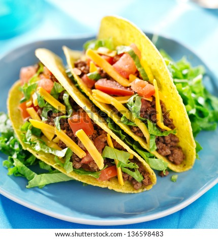 Mexican food - Hard shell tacos with beef, cheese, lettuce and tomatoes - stock photo