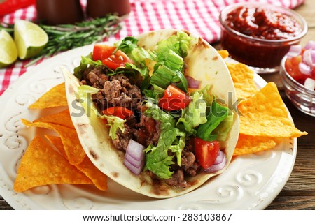 Mexican food Taco in plate on wooden table, closeup - stock photo