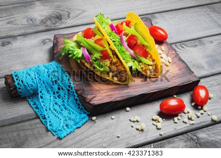 Mexican food tacos, peppers, cherry tomatoes, grated cheese, minced meat in a corn tortilla on board with blue lace, gray wooden background - stock photo