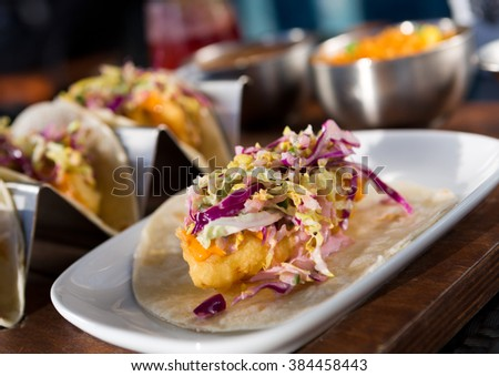 Mexican fried cod fish taco served with lettuce, red onion and sauce - stock photo