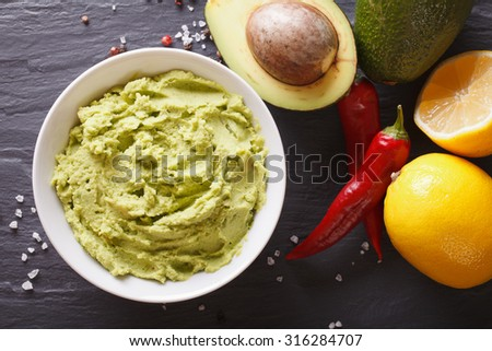 Mexican guacamole sauce with ingredients close-up on the table. horizontal view from above - stock photo