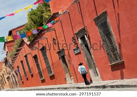 Mexican man passing in front of colorful colonial buildings in Zocalo Street of San Miguel De Allende, Mexico. - stock photo