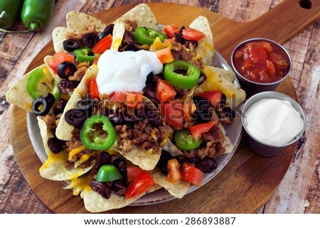 Mexican nacho chips topped with ground meat, jalapenos, tomatoes, beans and melted cheese with sour cream and salsa on a wooden paddle board - stock photo