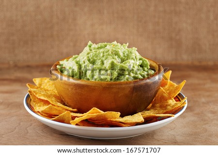 Mexican nachos with handmade guacamole sauce on wooden table - stock photo
