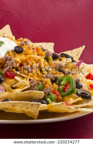 Mexican nachos with sour cream, black olives, ground beef, black beans, tomatoes, shredded cheese, jalapenos, rice, and cilantro - stock photo