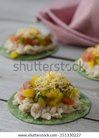 Mexican Pizzettes. tortillas with mashed white beans, tomatoes, cheese and bell peppers - stock photo