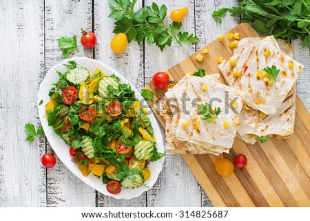 Mexican Quesadilla wrap with chicken, corn and sweet pepper and fresh salad. Top view - stock photo