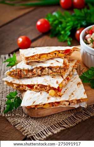 Mexican Quesadilla wrap with chicken, corn and sweet pepper and salsa - stock photo