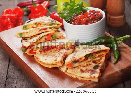 Mexican quesadillas with cheese, vegetables and salsa dipping sauce - stock photo