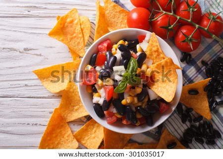 Mexican salsa with beans in a bowl and corn chips nachos on the table close-up. horizontal view from above