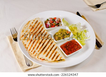 Mexican sauces, with hot tomato and chilli salsa, guacamole and diced spicy vegetables served with a corn tortilla with savory filling - stock photo
