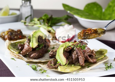 Mexican taco gourmet accompanied by avocado - stock photo